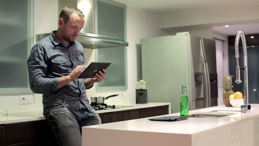 Young man with tablet computer standing in the kitchen