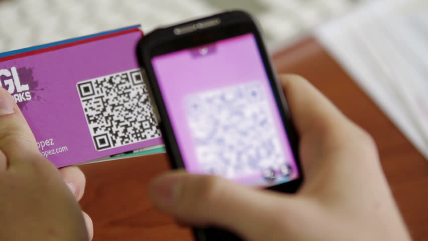 Business card being scanned by QR code to retrieve information, pull focus through the business card to the phone. Business card and QR Code was made specifically for this video. Royalty-Free Stock Footage #5172119
