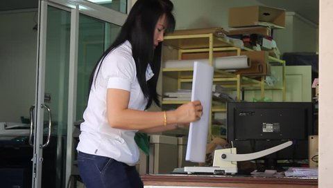 UDON THANI, THAILAND -DECEMBER 04, 2013: Worker have to do pagemaking for customer's document report at photo copier shop.