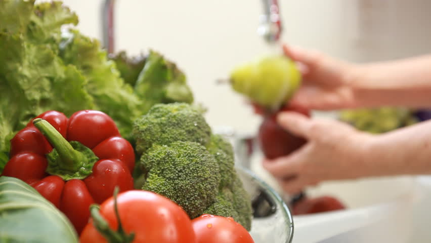 Camera focuses on an assortment of fresh vegetables with a woman washing fruit out of focus in the background.