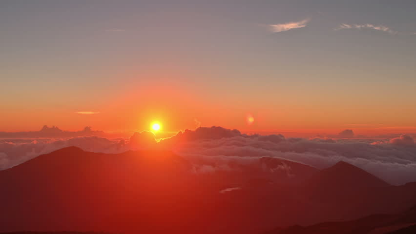 Red summit dawn above flowing cloud waves, red sun disk time lapse in HDR