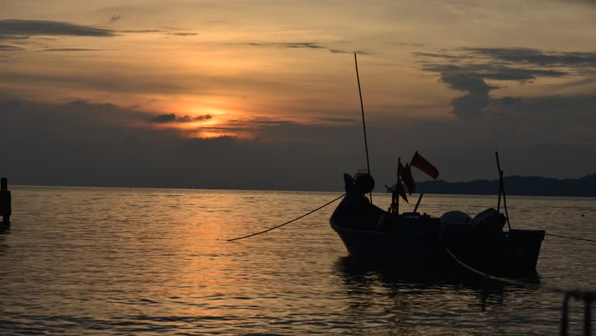 Time lapse of a silhouette wooden boat on the sea with sunset background | Shutterstock HD Video #5225486