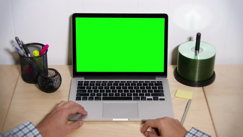 A man taps his fingers on his desk waiting for his laptop to operate. Green screen for your custom screen content. In 4K UltraHD.