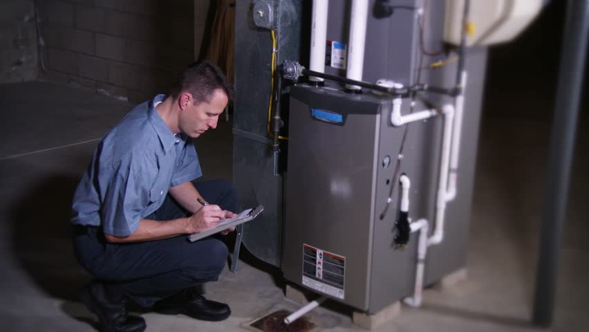A furnace serviceman inspects a household furnace.