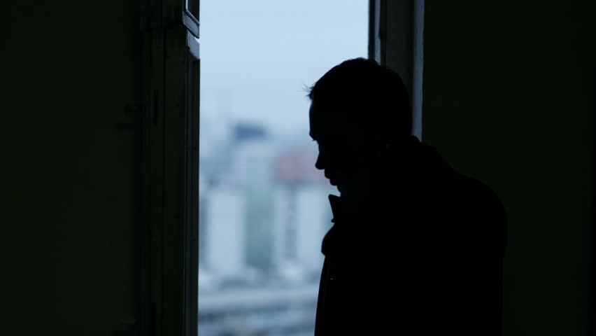 Man talking on the phone near the window. Black silhouette on blurry city background in the window. | Shutterstock HD Video #5247362