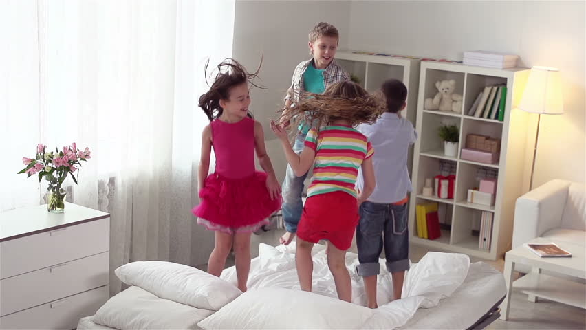 Four energetic friends spending their weekend together jumping on the bed | Shutterstock HD Video #5251778
