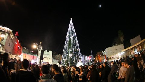 NAZARETH, ISRAEL - DECEMBER 16: People visit the Christmas tree near the Greek Orthodox Church of the Annunciation in Nazareth, Israel, November 16, 2013