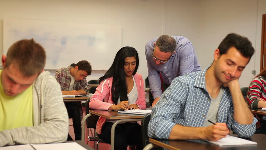 Teacher explaining something to student in class in a college | Shutterstock HD Video #5270531