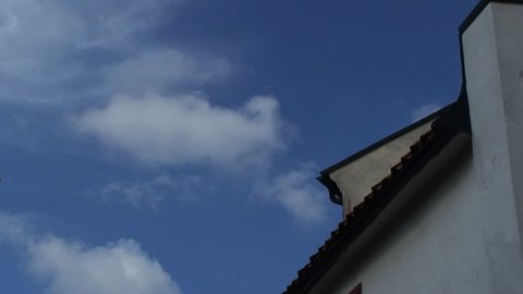 Clouds in timelapse rolling over a house roof