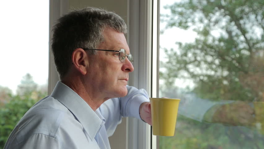 Close up, middle aged man looks out of window drink from a cup and turns to camera | Shutterstock HD Video #5297870