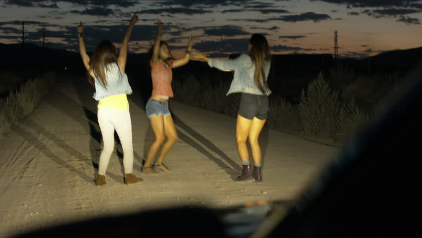 Young Women Dancing/Celebrating In A Car's Headlights
