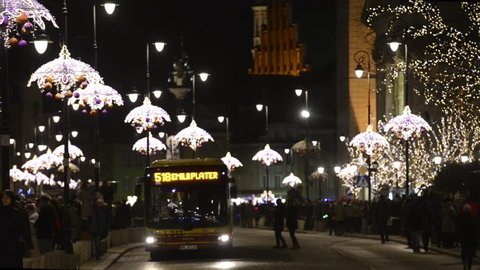 WARSAW, POLAND - DECEMBER 25: Undefined tourists on the street during Christmas on December 25, 2013 in Warsaw, Poland. The modern colorful Christmas lights attract and encourage people to the street.