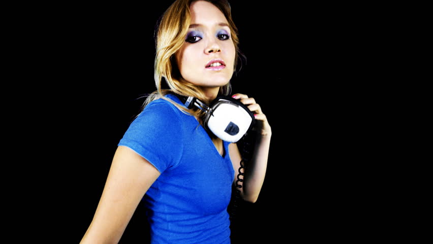 Beautiful young blond woman dances in tight top and headphones | Shutterstock HD Video #532387