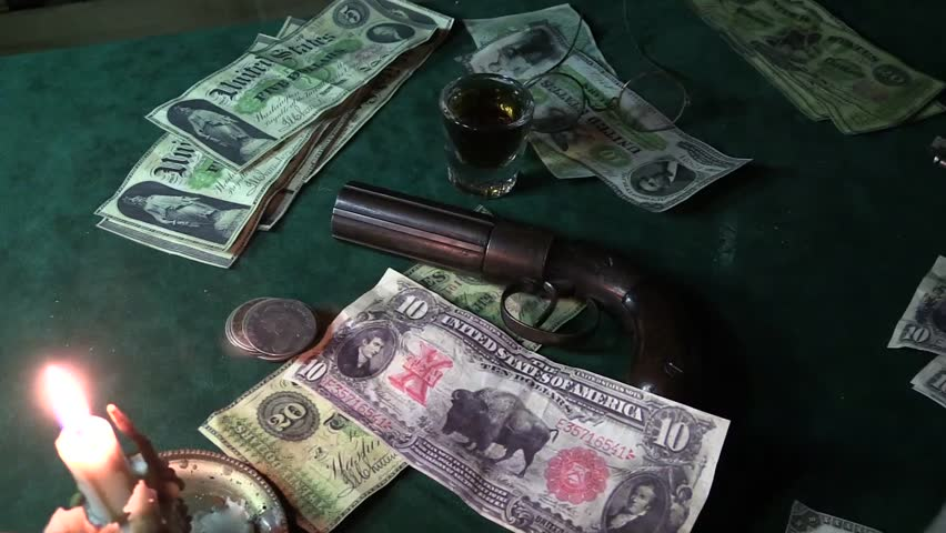 Cowboy gambler in a saloon casino playing and betting antique money on a poker game. Playing by candlelight you can see a old pepper box pistol, paper currency and silver coins. | Shutterstock HD Video #5347418
