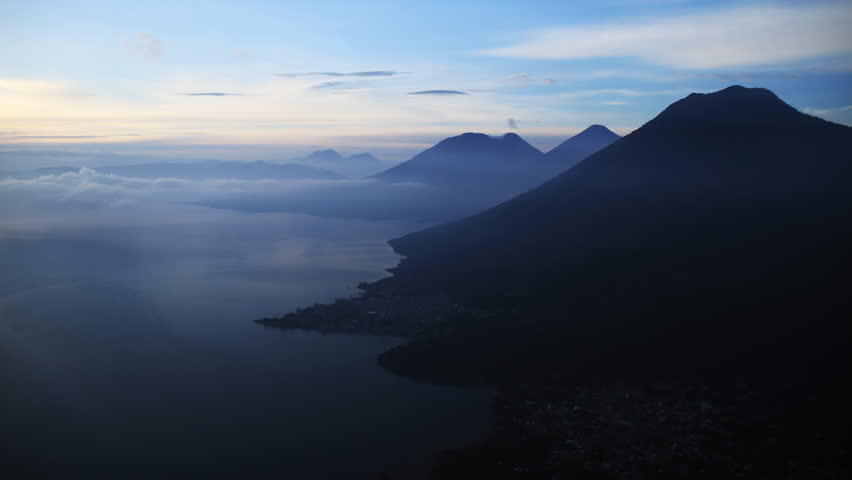 A time-lapse shot of a sunrise from the peak of the Indian Nose overlooking Lake Atitlan in Guatemala. Three volcano peaks can be seen as the sun rises.