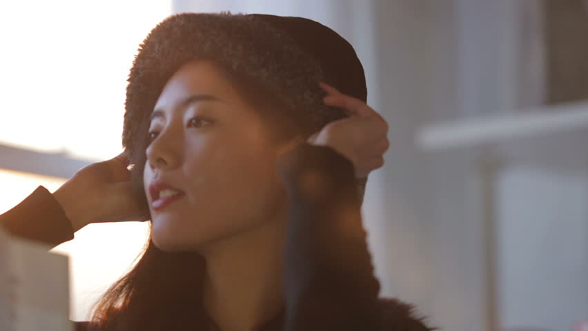 Close up clip, with natural sunlight flare, of a beautiful asian woman taking her newly bought hat from a shopping bag & trying it on. Royalty-Free Stock Footage #5360351