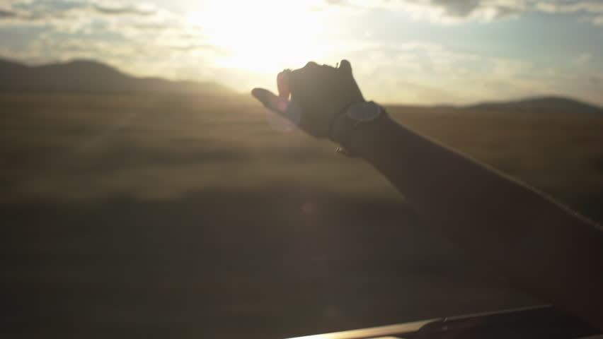 Teen Waves Her Hand In The Wind In A Convertible