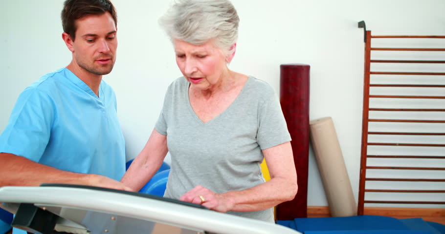 Physical therapist showing patient how to use exercise machine at the rehabilitation center