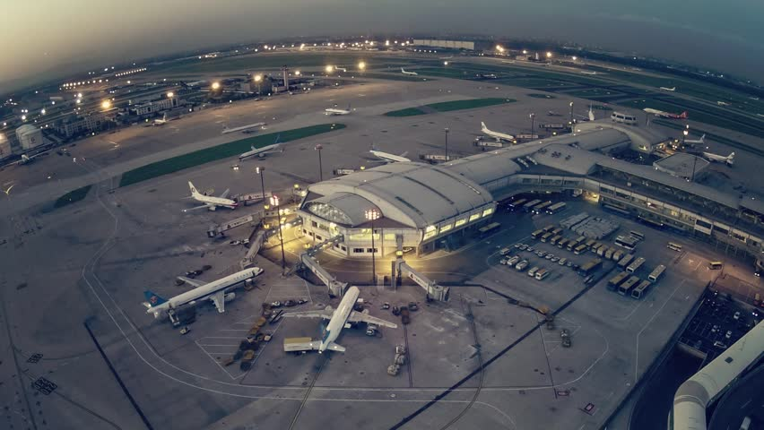 Timelapse.Aerial View.Airport Terminal at Sunset with Airplanes Taxiing and Landing.