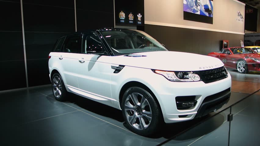 BRUSSELS, BELGIUM - JANUARY 14, 2014: Range Rover Sport (L494) luxury-type sport utility vehicle on display at the 2014 Brussels motor show. A woman is walking past the car in the background.  #5426639