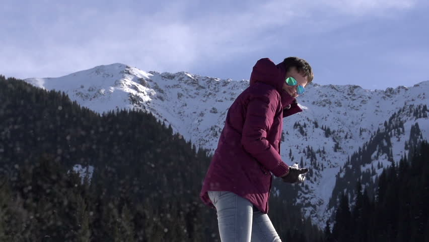 Winter Resort. Young woman throwing snowballs on a background of snowy mountains and blue sky. Slow Motion at a rate of 240 fps | Shutterstock HD Video #5441303