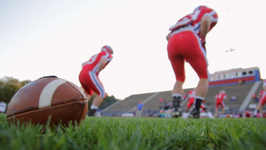 Football players warming up as a team with a football in the foreground.