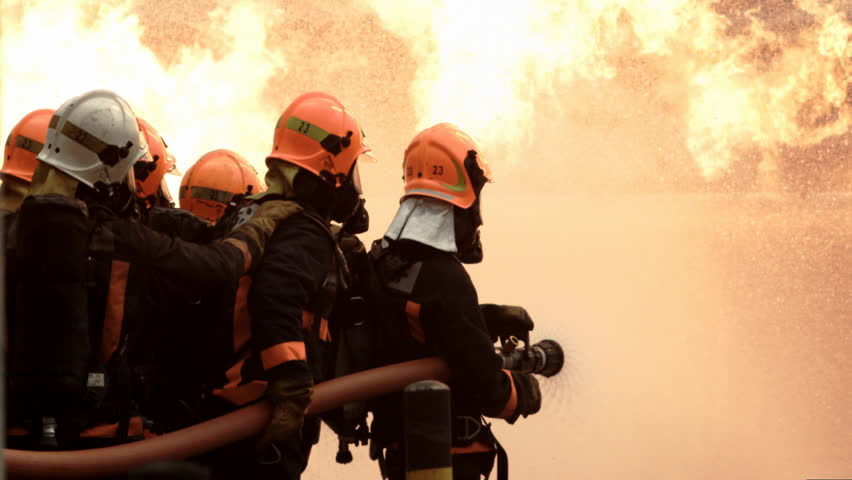 A team of fire fighters hold a hose and put out a house fire | Shutterstock HD Video #5453789