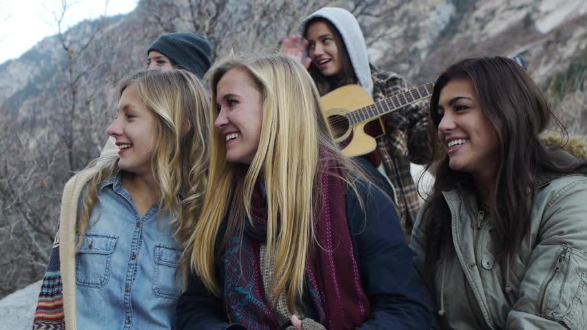 Five Bundled Up Teen Girls, One Playing Guitar, Four Waving At Friends Off-screen #5459570