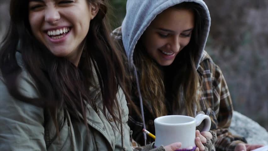 Two Teen Girls Bundled Up Outdoors, Enjoying Something On Paper   Shutterstock HD Video #5460164