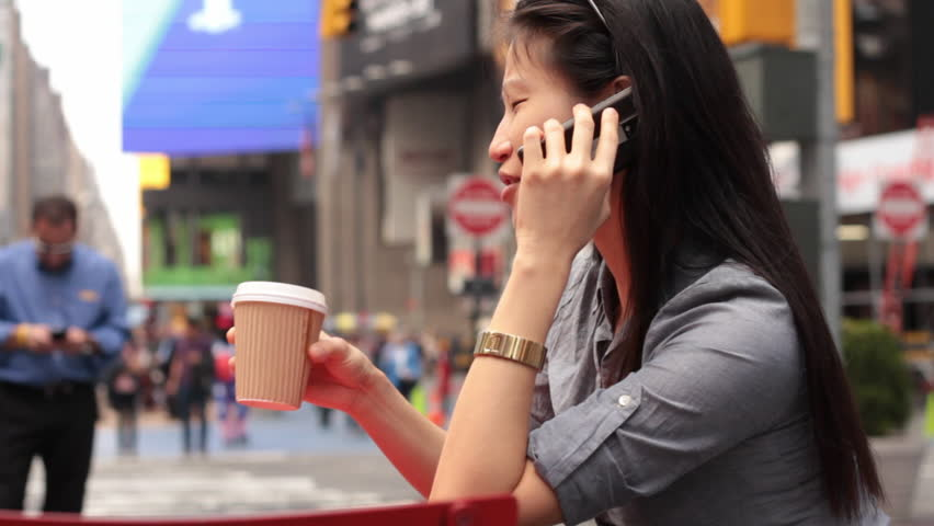 A young woman chats on her phone with a cup of coffee, amongst the chaos of Times Square, New York   Shutterstock HD Video #5467841