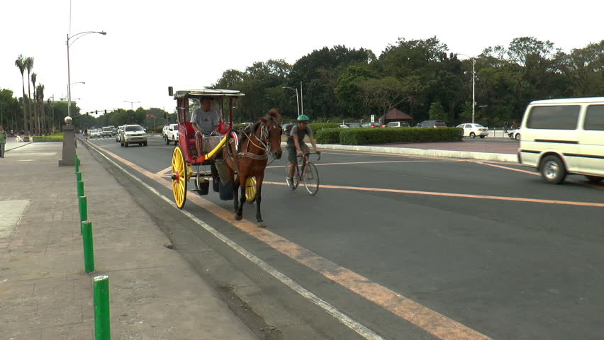 MANILA, PH - JANUARY 22: Horse-drawn carriage, and cars passing a not too busy street front of Rizal park in Manila Philippines on January 22, 2014.    Shutterstock HD Video #5482439