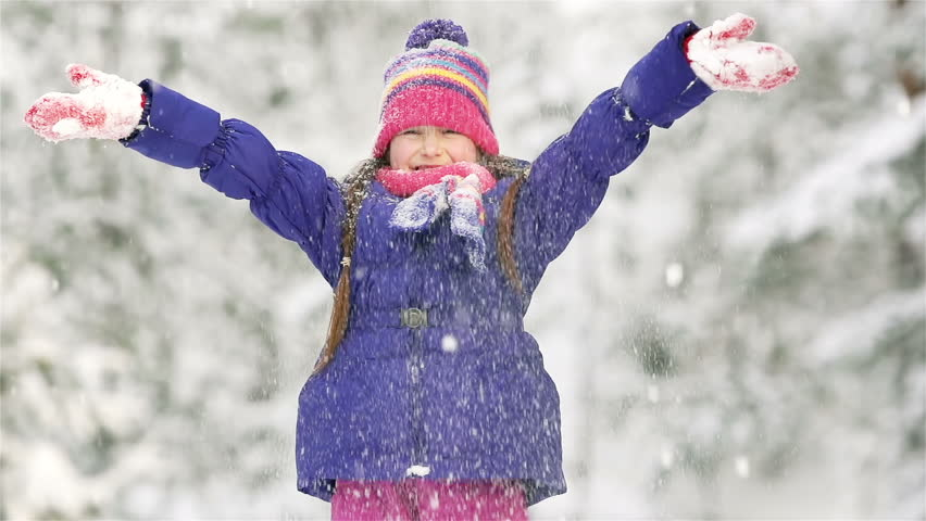 Lovely little girl throwing a handful of snow up in the air
