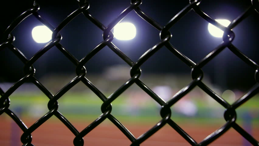 Dolly of a fenced in stadium at night, with the focus on the fence. #5492234