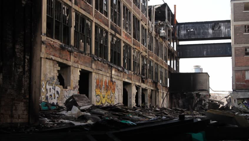 Detroit, MI. - Circa 2013 - A lone man walks through the debris and rubble of an abandoned industrial site in Detroit, MI.