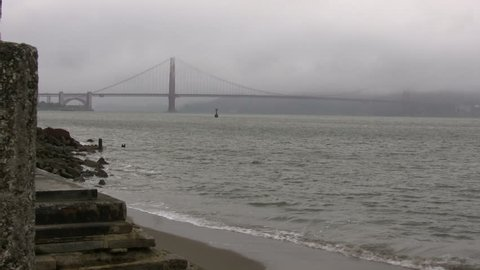 Distant view of the Golden Gate Bridge on a foggy day. Waves are gently washing up on the beach in the foreground.