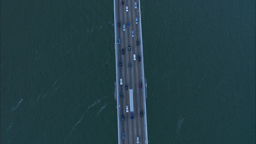 San Francisco City Bay Bridge. A skying view over the Bay Bridge in San Francisco, California. The shot captures the busy trafficked bridge. | Shutterstock HD Video #5514488