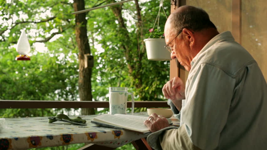 Senior man, relaxing and reading a book, while sitting outside in front of a cabin on a lake. | Shutterstock HD Video #5538620