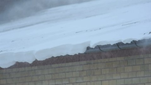Snow blowing of an apartment roof during a blizzard