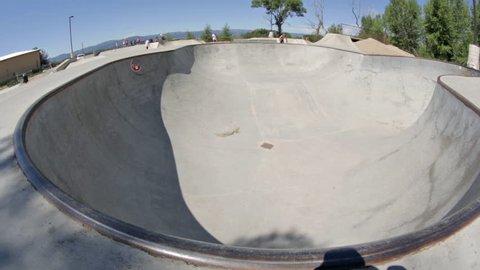 A BMX biker rides around the rim of a bowl at a skate park