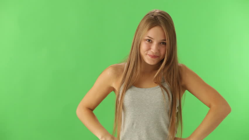 Cute young woman standing on green background expressing astonishment looking at camera and smiling | Shutterstock HD Video #5561651