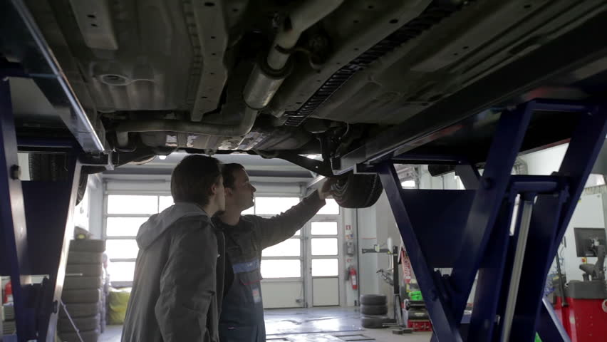 Mechanic and the car owner stand under the car and debate the issues   Shutterstock HD Video #5568716