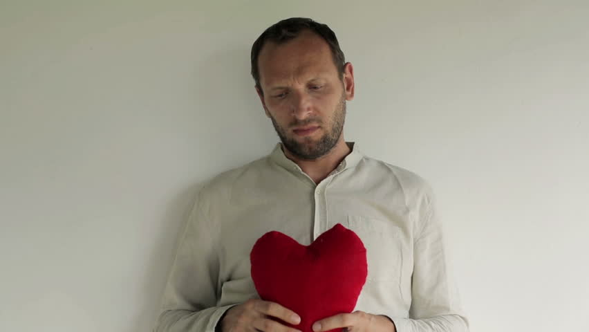 Angry, unhappy man with heart shape pillow  | Shutterstock HD Video #5574686