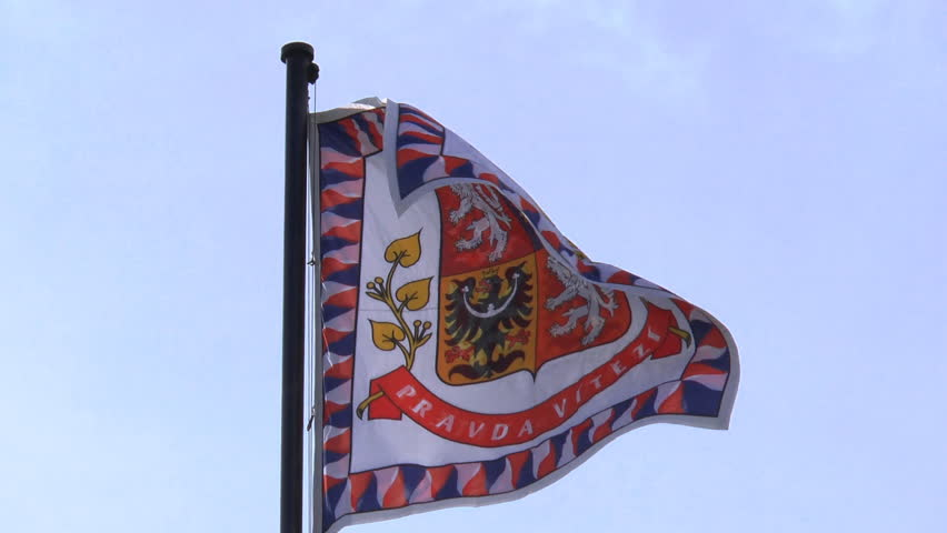 A flag with the Coat of arms of the Czech Republic flying against a blue sky at Prague Castle, in the Palace of Prague, Slow Motion #5579234