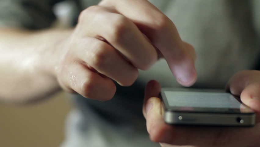Tracking shot of a male using a cell / mobile phone close up and shallow focus Royalty-Free Stock Footage #5580158
