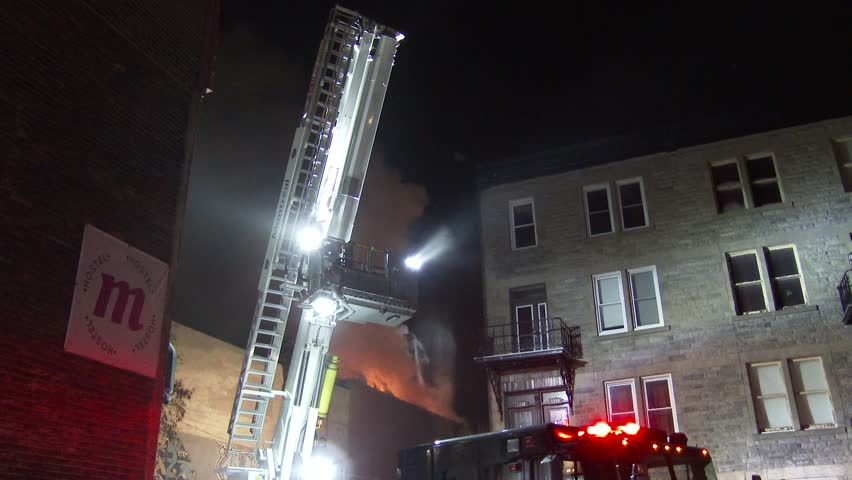 MONTREAL, QC - JAN 2014 - 4K UHD - Firetruck aerial platform unfolding. A high-tech 125 foot high ladder of a firetruck is unfolding and extending at night with a house on fire in the background.