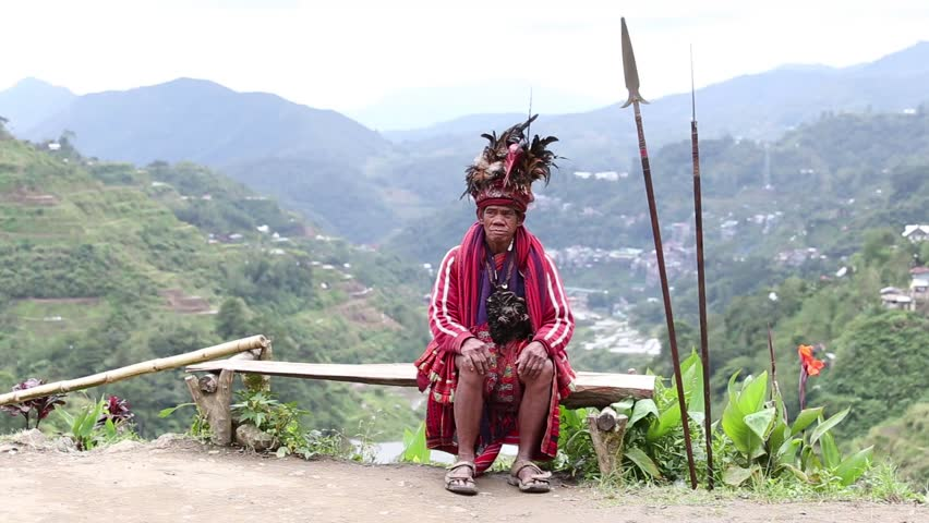 BANAUE, PHILIPPINES - JANUARY 24, 2014 : Unknown old ifugao man in national dress next to rice terraces. Ifugao - the people in the Philippines. Refers to the mountain peoples.