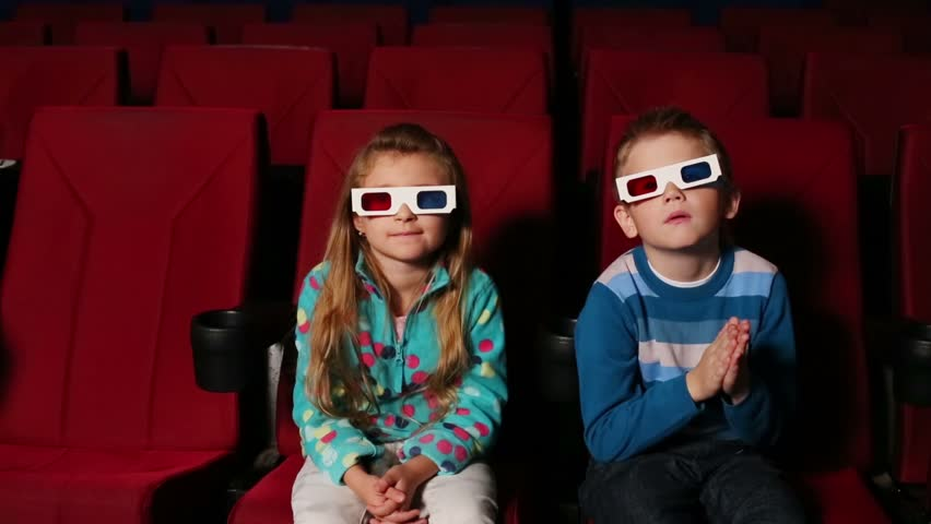 Little boy and girl in 3D glasses sit on the front row of the auditorium and watching a movie