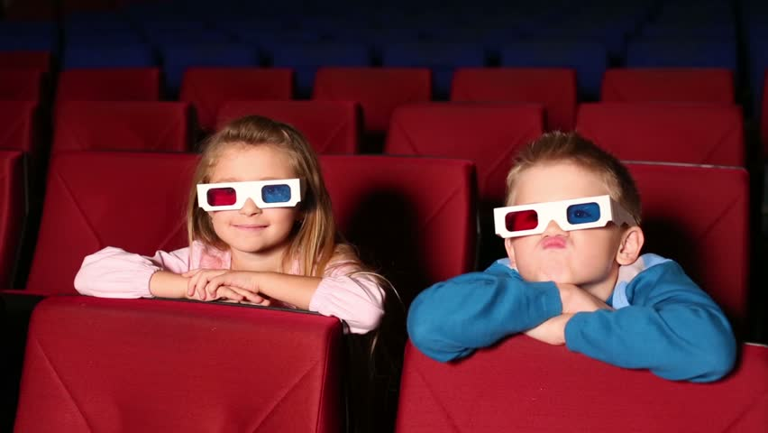 Little girl and boy in the red-blue 3D glasses in the cinema watching a movie