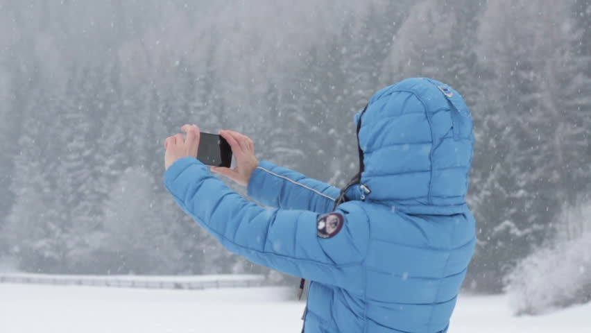 Young woman uses a smartphone to video a beautiful view in winter scenery, slow motion