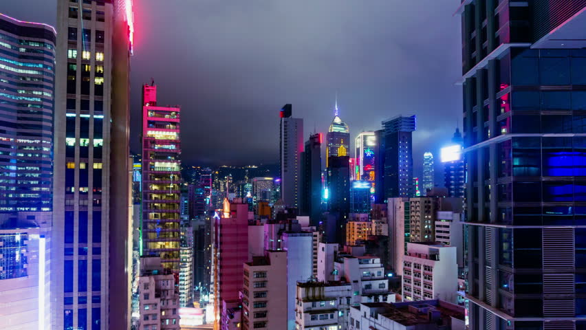 City Night Timelapse. 4K Zoom In Shot. Attractive Hong Kong night timelapse. Commercial office buildings, commercial LED flashing billboards and residential buildings. Fast moving cloud on the sky.